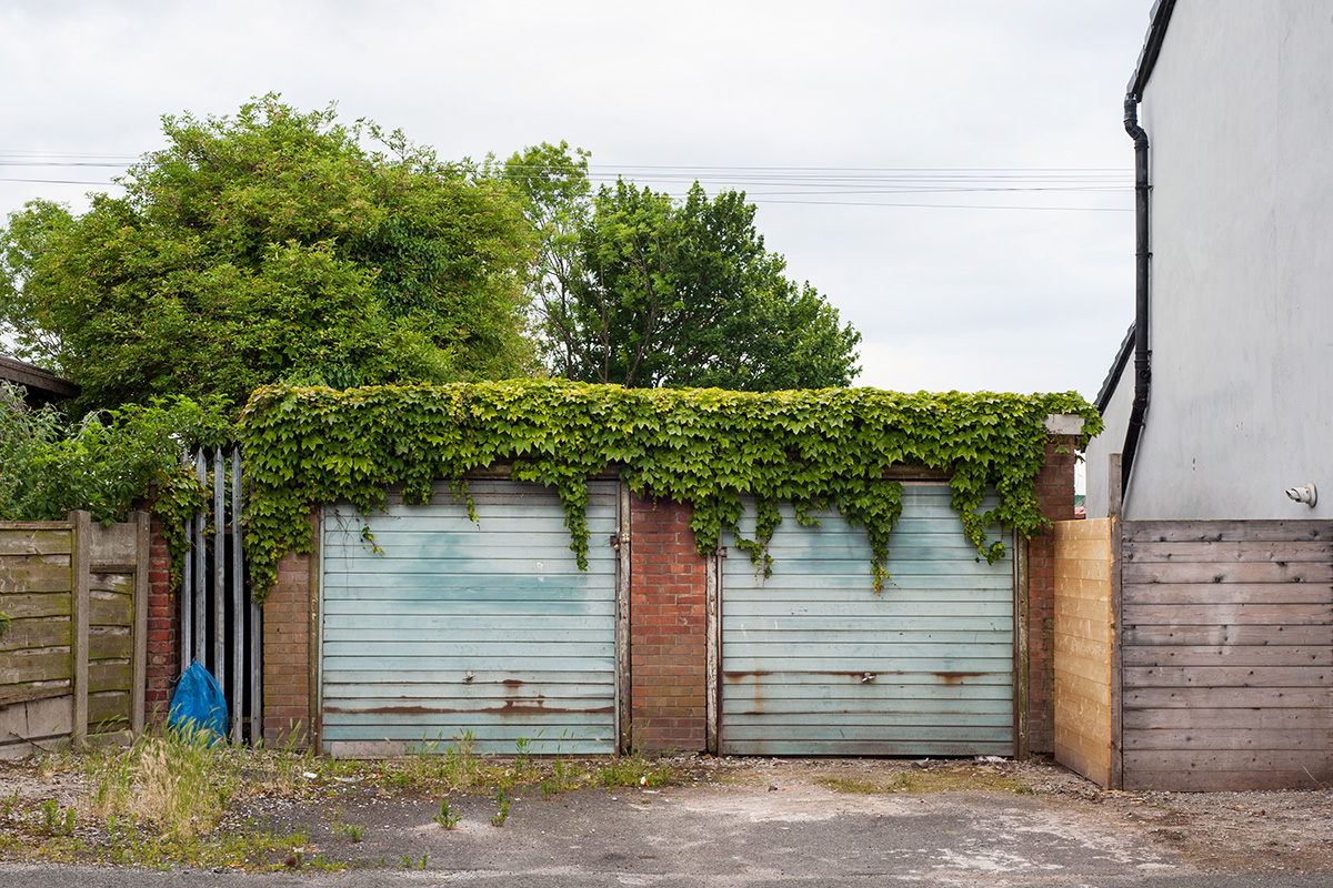 Two garages overhanging with ivy