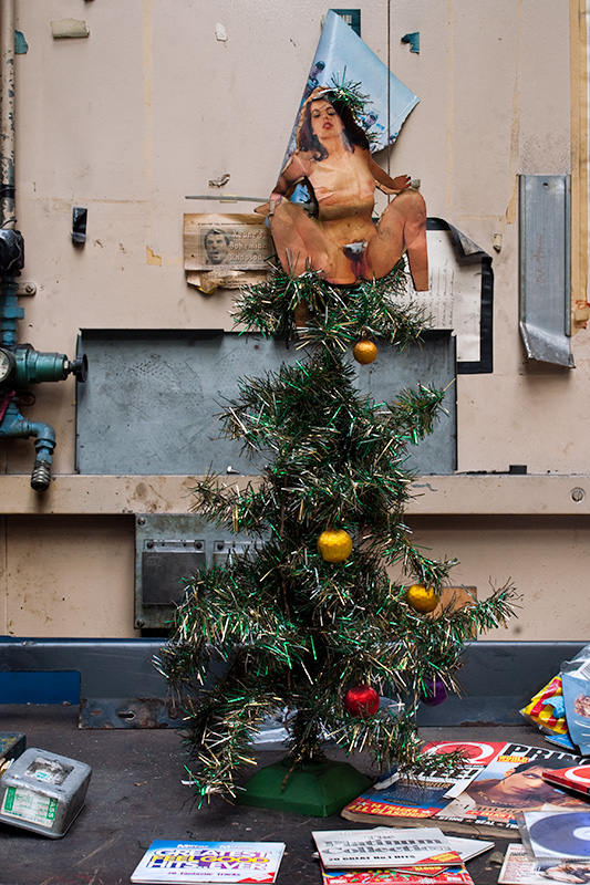 A Christmas tree, with nude woman in place of an angel