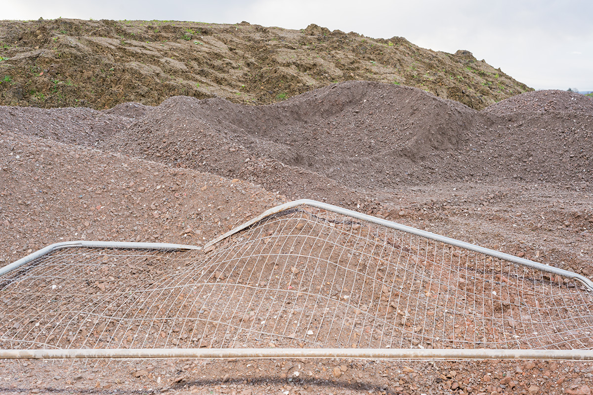 A bent piece of Heras fencing atop a pile of gravel, with the mesh giving the appearance of a topographic map