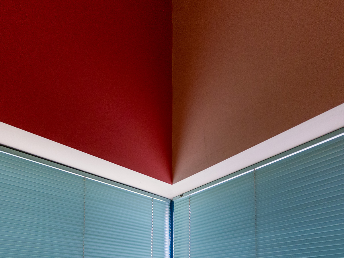 A room interior with contrasting red walls and blue blinds