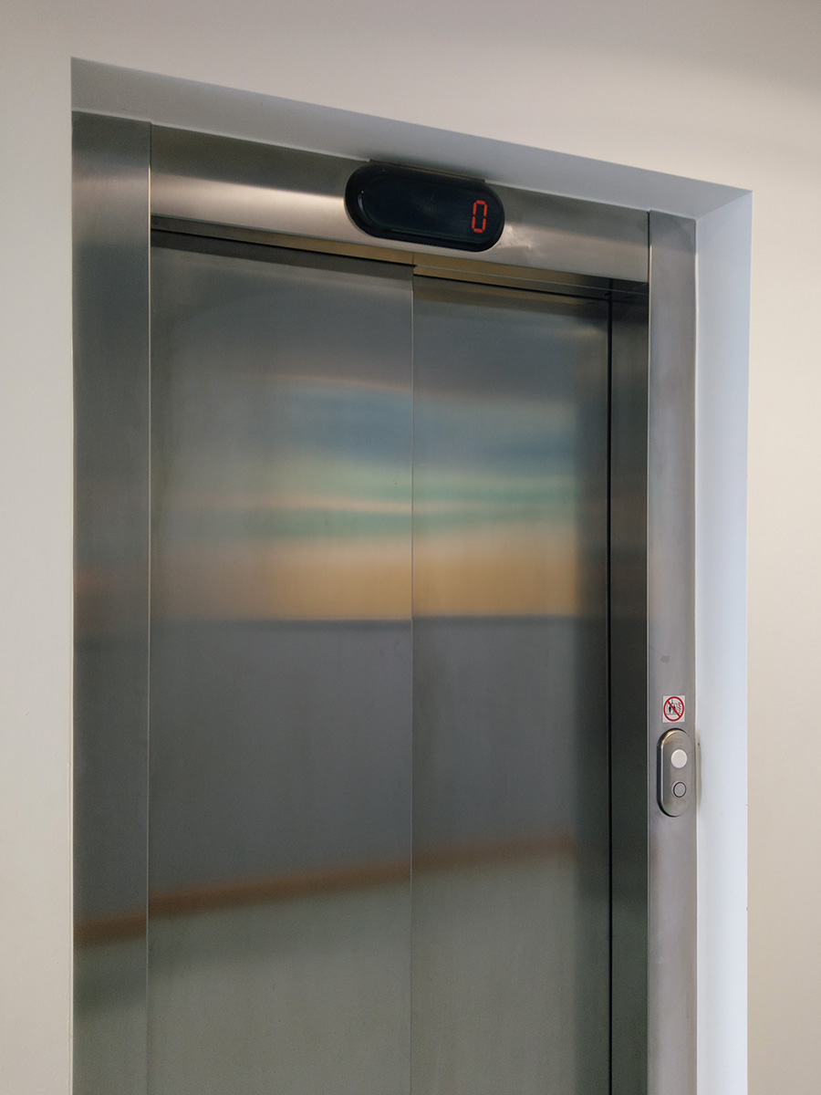 Reflection of an abstract painting in metal elevator doors in a hospital