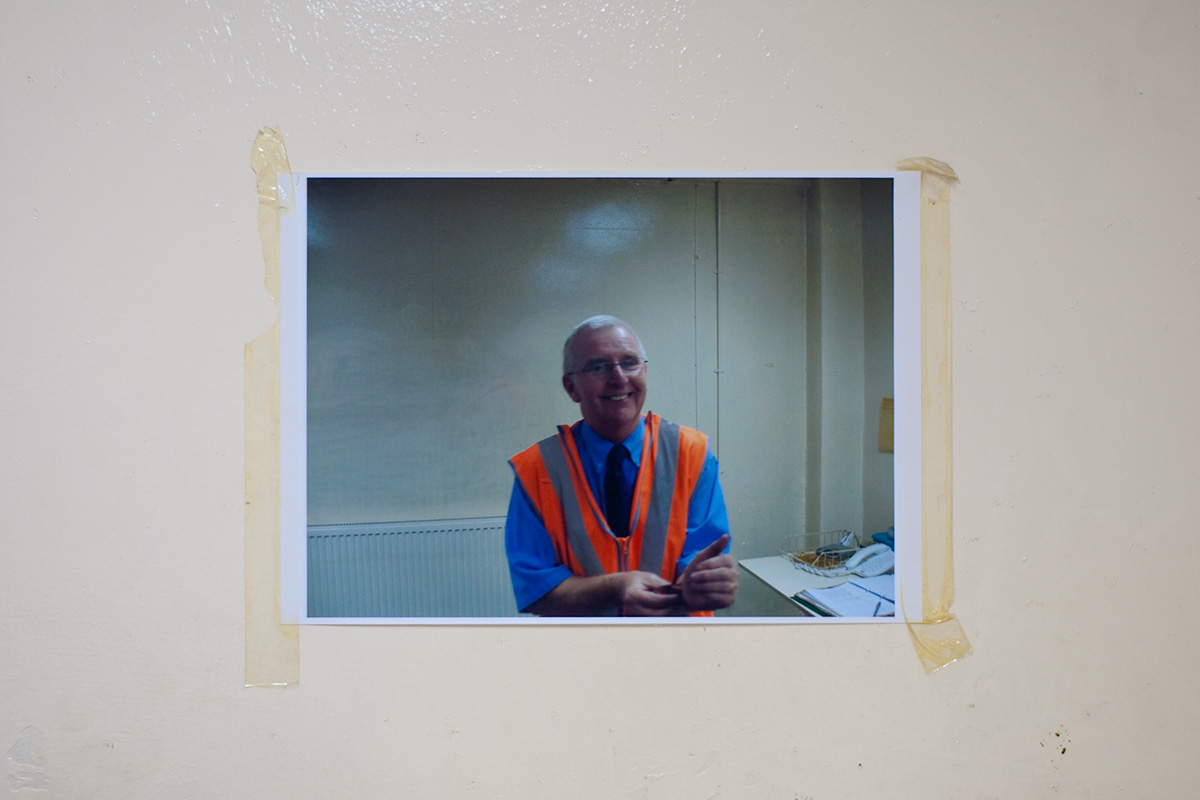 A photograph of a member of staff, taped to a wall