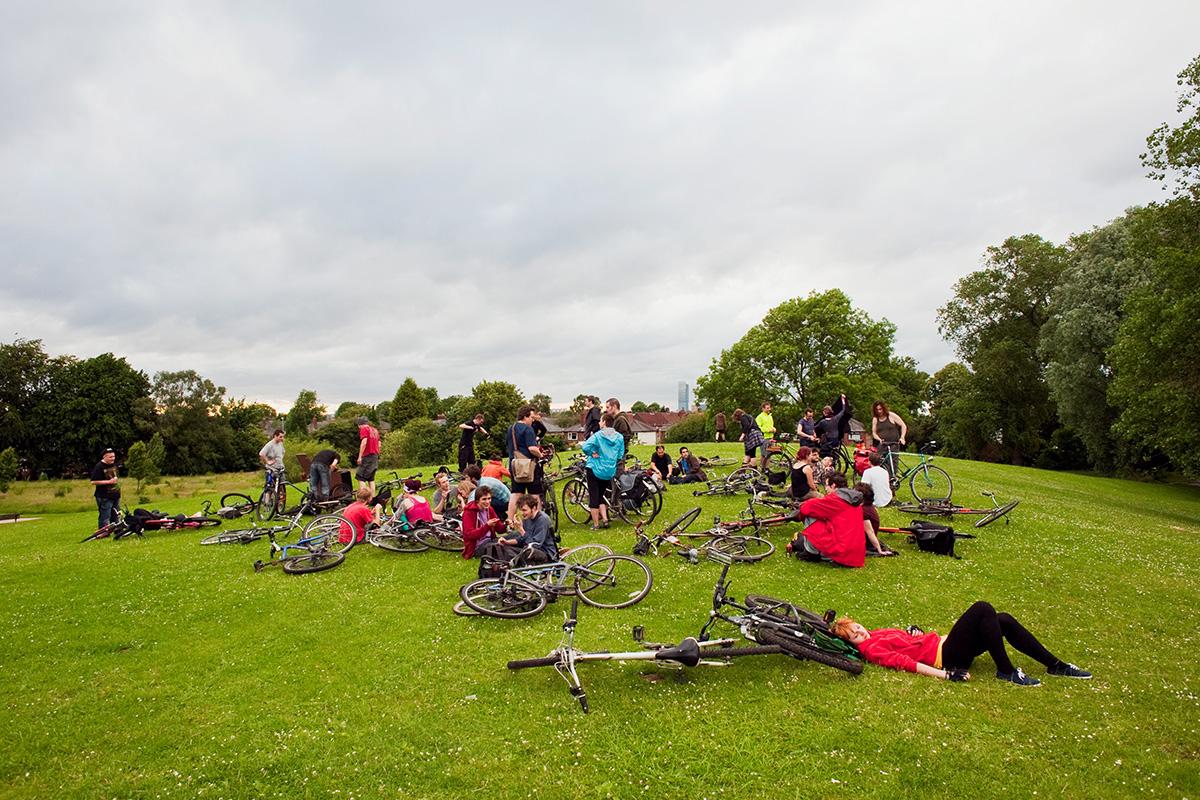 Cyclists gather in Platt Fields Park after a monthly Critical Mass ride