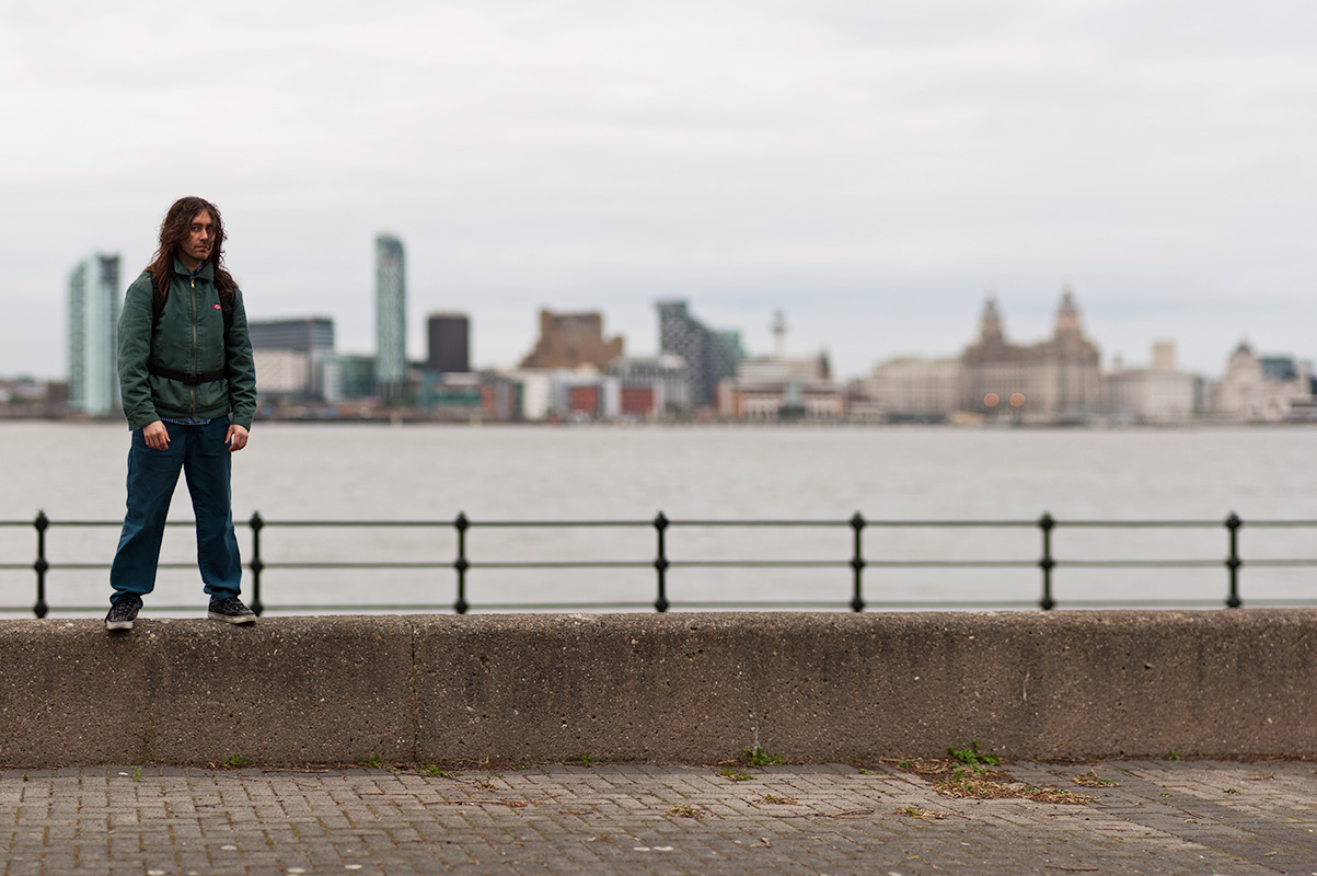 Brian on the Wallasey waterfront, with Liverpool beyond