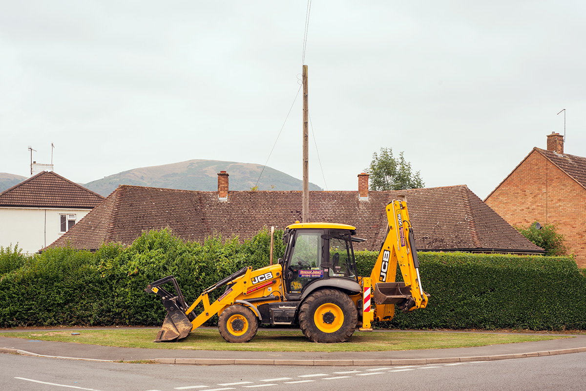 A JCB parked on a grass verge in Barnards Green, Worcestershire before the Malvern Hills