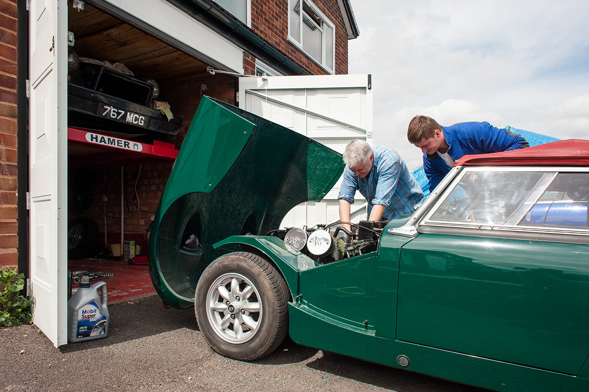 A father and son working on an Austin Healey on a driveway in Hollywood, Worcestershire