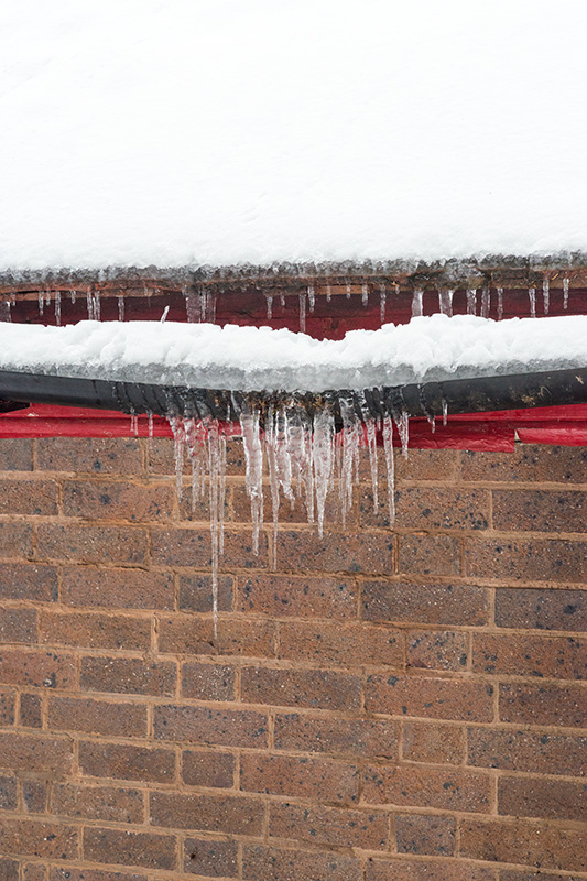 Icicles hanging from bowing guttering on a building in Priory Park, Great Malvern