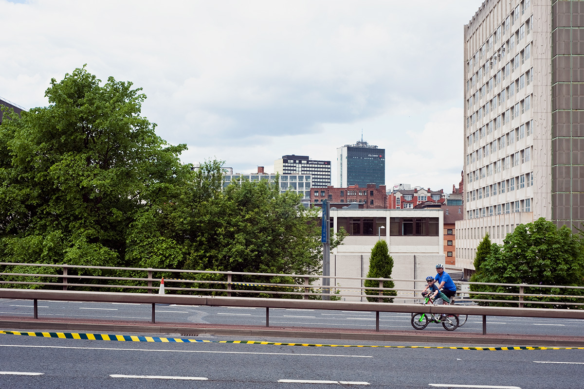 A father and son participating in the Great Manchester Cycle, riding along the Mancunian Way where it crosses Upper Brook Street