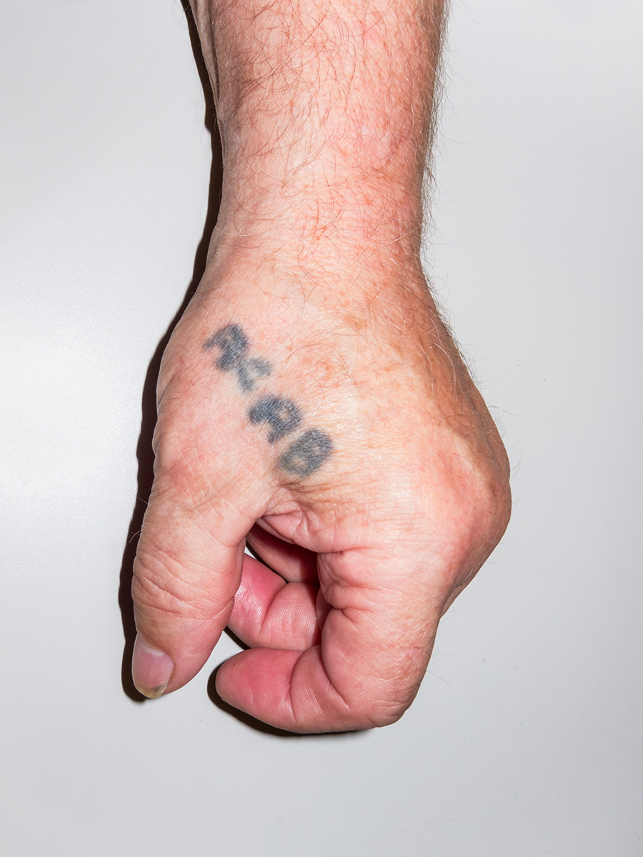 A hand tattoo reading ACAB