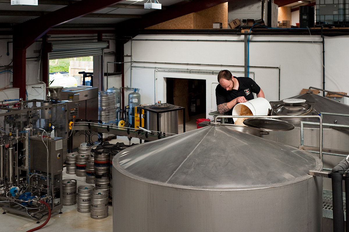 Colin Stronge pitching yeast into a fermenting vessel at Black Isle Brewery