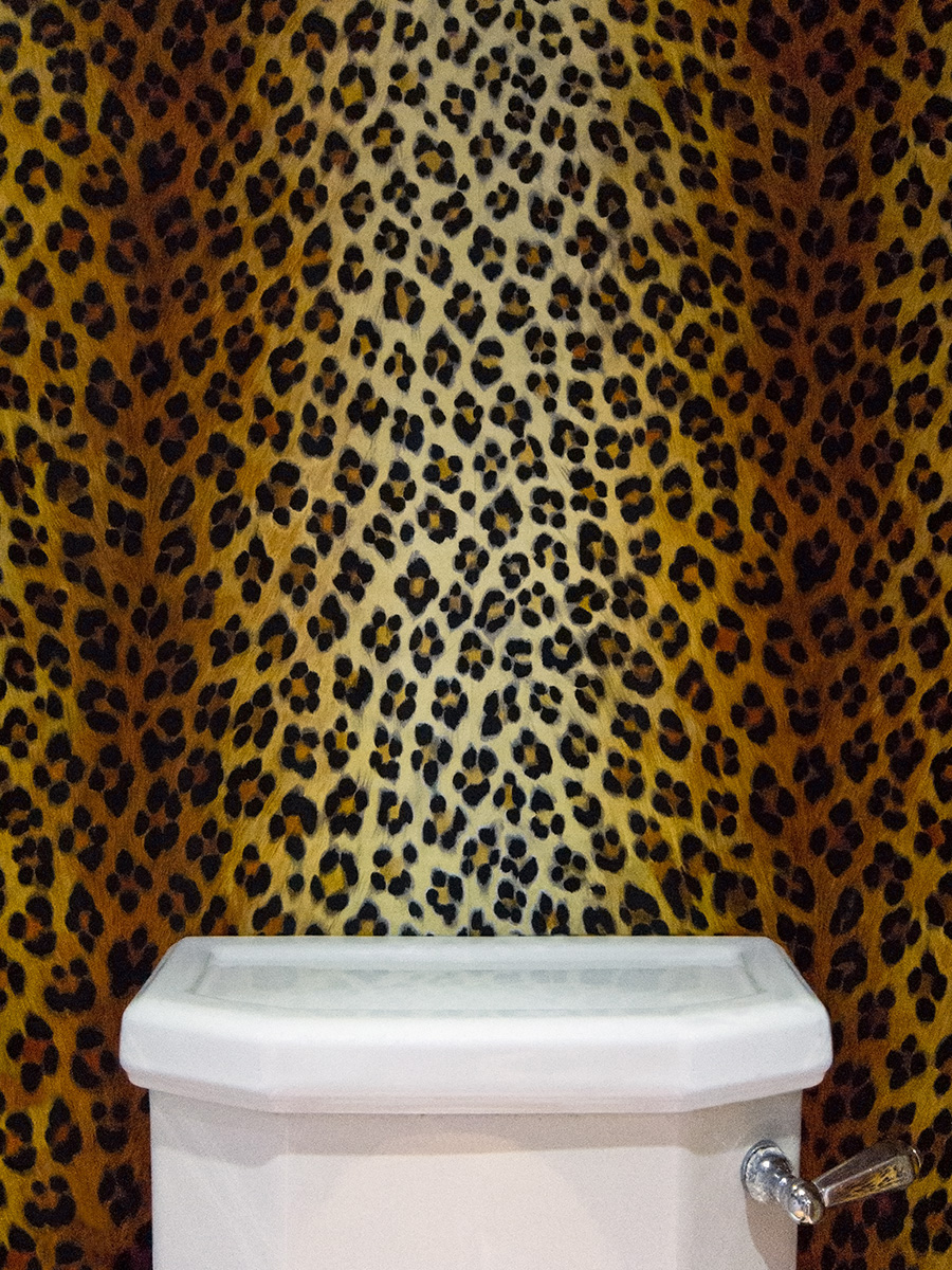 A toilet with leopardskin wallpaper