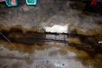 A reflection of shelves in an oily puddle in a bus maintenance area