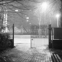 The gates of Platt Fields Park at night