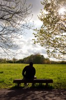 A man sitting on a bench, enjoying the view across a meadow area of Fletcher Moss, Didsbury, Manchester