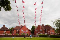 Children play football beneath Jubilee bunting on Platt Lane, Fallowfield