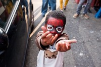 A boy wearing Spiderman face paint pretending to shoot web from his hands