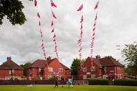 Children play football beneath Jubilee bunting on Platt Lane, Fallowfield